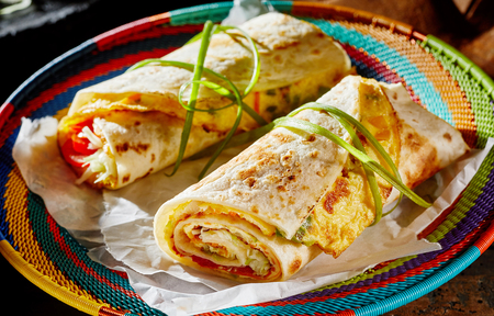 Ugandan Rolex Rolls street food on a brightly colored basket with egg omelette and vegetables rolled in a fried chapati Stock Photo