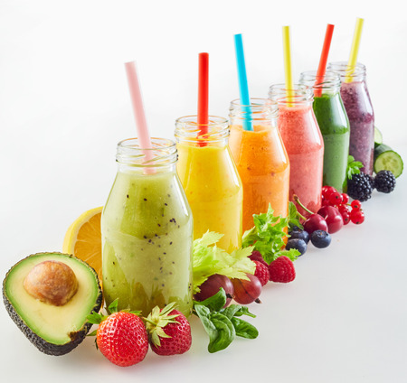 Receding diagonal row of different fresh fruit and vegetable smoothies with colourful ripe ingredients on white with copy space for a healthy nutritious diet