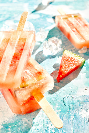 Fresh watermelon frozen fruit popsicles for a delicious summer treat on blue with crushed ice and focus to a slice of the melon 스톡 콘텐츠