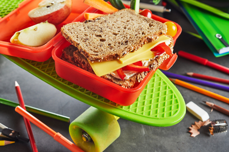 Kids red plastic school lunch box with healthy cheese and tomato sandwich on wholewheat bread and sliced apple on a bright green roller skate with scattered pencil crayons