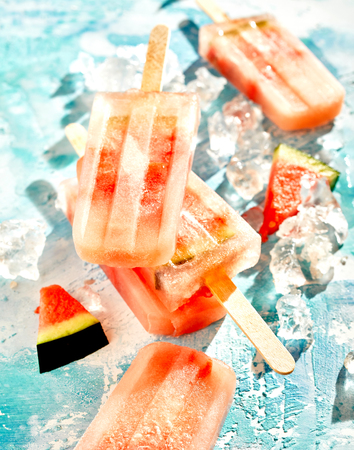 Homemade frozen fresh watermelon popsicles or iced lollies with sliced fresh melon on crushed ice in a close up view 写真素材