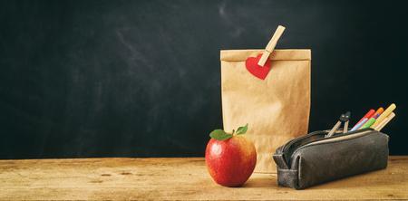 Almuerzo bolsa marrón sellada con corazón rojo y pinza para la ropa junto a la manzana y la bolsa de la pluma en la mesa con fondo negro Foto de archivo - 104943709