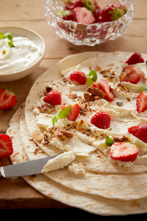 Making delicious fresh strawberry and whipped cream wraps with chopped nuts and mint in a close up view on a kitchen table