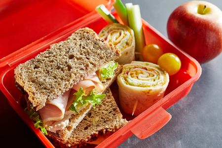 Colorful red plastic kids lunch box filled with healthy food including fresh vegetables, a wholewheat ham sandwich and Rolex Roll on chappati with a fresh apple alongside