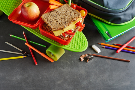Kids school lunch box, skate and backpack with spilled pencil crayons and an apple, veggies and cheese on tomato sandwich on healthy wholegrain bread, copy space below Banco de Imagens - 104943510