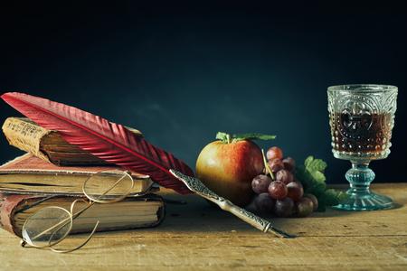 Vintage martwa natura na studia lub pisarza z piórem gęsim piórem i okularami do czytania spoczywającymi na starych książkach obok świeżych winogron, jabłka i kielich wina na starym drewnianym stole z miejscem na kopię