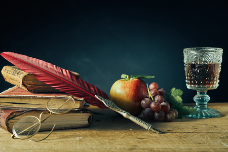 Vintage stilleven voor college of een schrijver met een veer ganzenveer en leesbril rustend op oude boeken naast verse druiven, een appel en een beker wijn op een oude houten tafel met kopie ruimte