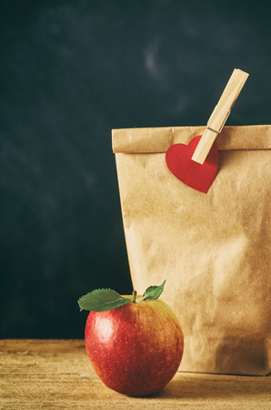 Close up on delicious red apple and brown bag lunch closed with clothespin. Includes copy space.