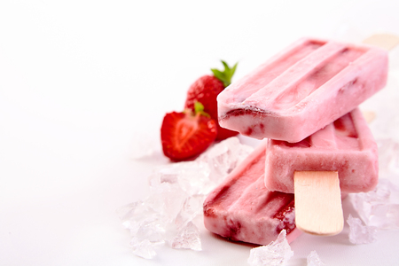 Three frozen popsicles with fresh strawberry ingredients stacked chilling on a bed of crushed ice with copy space alongside Stock Photo