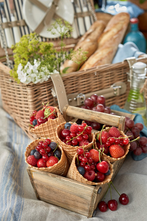 Selection of fresh berries displayed in cornets or ice cream cones in an old wooden box at a picnic with raspberries, strawberries, blueberries and cherries