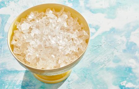 Recipiente amarillo de hielo limpio triturado para usar como ingrediente en la cocina o bebidas sobre un fondo azul moteado fresco con espacio de copia Foto de archivo