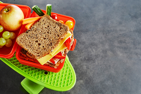 Kids school lunch box with a healthy fresh snack including a wholegrain cheese and tomato sandwich, vegetables, apple and grapes viewed from above on a bright green roller skate over slate