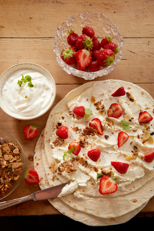 Preparing fresh strawberry and cream wraps with chopped nuts and mint in an overhead view with ingredients on a wooden table Stock Photo