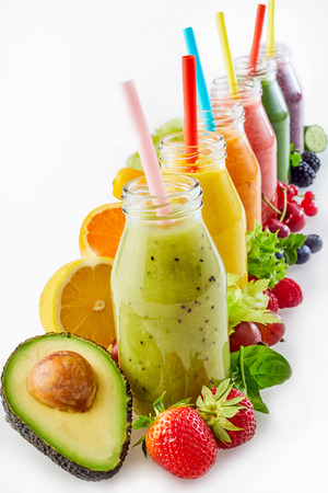 Healthy vegetable and fruit smoothies in glass bottles with straws arranged in a receding row surrounded by the fresh ingredients over white with copy space for a healthy diet Stock Photo