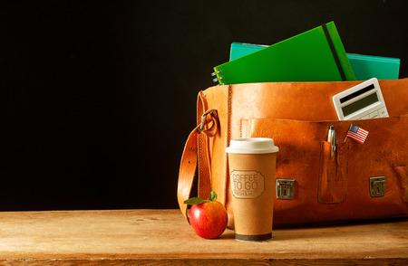 Skórzana teczka z kalkulatorem, notesami, przypinką z amerykańską flagą i filiżanką kawy obok pysznego czerwonego jabłka