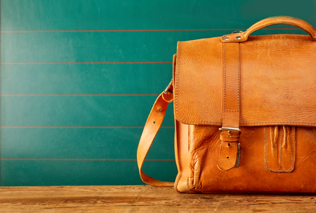 Closed leather backpack case with copy space over green wall and old wooden table Standard-Bild - 105071939