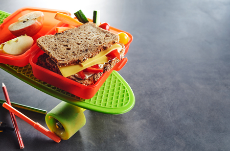 Red plastic kids school lunch box with a healthy wholegrain cheese and tomato sandwich, sliced fresh apple and vegetables for a tasty snack Stock Photo