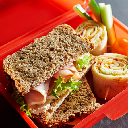 Tasty ham sandwich on wholegrain bread with a rolex roll and diced veggies in a red plastic school lunchbox in a close up cropped view