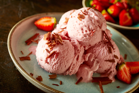 Strawberry ice cream balls served on plate sprinkled with chocolate Zdjęcie Seryjne - 105071952