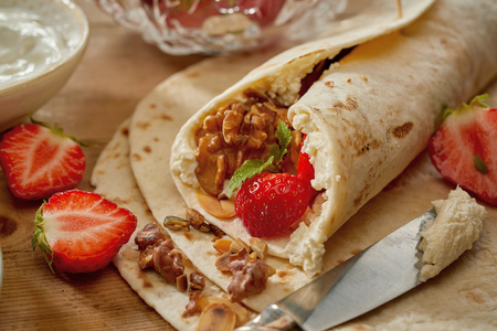Making strawberry, walnut and cream wraps on a kitchen table in a close up view of the rolled end of the filled pancake or tortilla