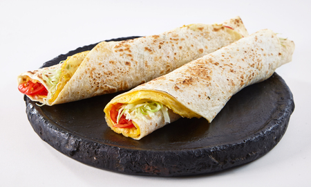 Tasty African rolex roll wraps with omelette served on black wooden tray Stock Photo