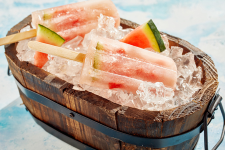 Refreshing healthy frozen watermelon popsicles in a wooden tub chilling on crushed ice with slices of fruit ready for a party 스톡 콘텐츠