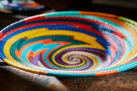 カラフルな先住民織りのアフリカのボウルと明るい螺旋パターを持つ近い低角度のトリミングビュー