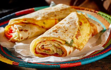 Two delicious indigenous Ugandan Rolex Rolls made with egg omelette and diced fresh vegetables rolled in a chapati or roti on a colorful woven basket Stock Photo