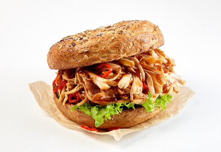 Pulled chicken kebab burger on a wholegrain bun with spicy hot chili pepper and lettuce served on paper over white