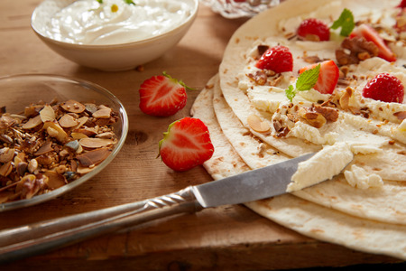 Gourmet strawberry wraps with whipped cream and chopped mixed nuts garnished with mint during preparation on a wooden kitchen counter