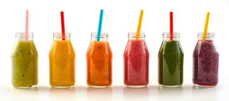 Panorama of assorted healthy colorful fresh fruit and vegetable smoothies in glass jars with straws on a reflective white background