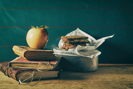 Old vintage school still life with tin lunch box and healthy wholegrain sandwiches beside a stack of worn books and metal rimmed spectacles Stock Photo