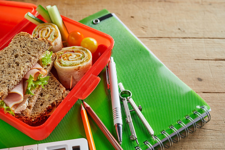 Kids school lunch box with ham sandwich, Rolex rolls and diced fresh vegetables open on a class notebook with pens, pencil and compass Stock Photo