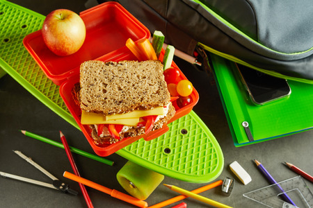 School lunch break with wholegrain cheese sandwich in a colorful red plastic box alongside notebook and pens and a bright green roller skate