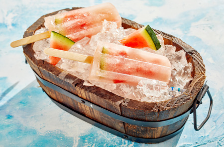Rustic wooden tub filled with crushed ice and fresh watermelon popsicles with slices of fruit for a healthy summer snack