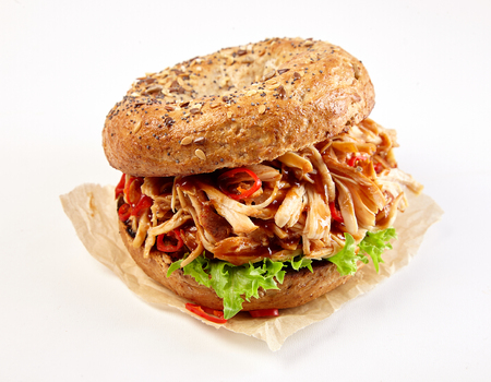 Pulled chicken kebab burger with spicy chili and lettuce on a healthy wholewheat bun over a white background Stock fotó - 105071992