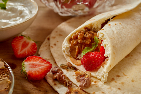 Homemade strawberry and walnut wraps with fresh whipped cream and mint in a close up view of the rolled end surrounded by ingredients