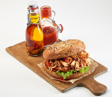 Delicious spicy pulled chicken sandwich or burger on a wholegrain bun served on a wooden board with bottles of ketchup and olive oil dressings isolated on white