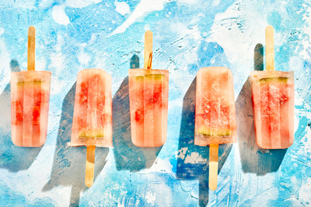 Flat lay still life of a row of homemade frozen iced melon popsicles made with fresh summer fruit on a mottled blue background in alternating directions Reklamní fotografie - 105072008