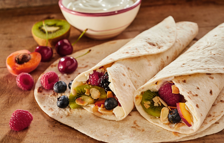 Two delicious healthy tropical fruit wraps layered with whipped cream and garnished with chopped nuts in a close up view for a menu or advertising with ingredients Stock Photo