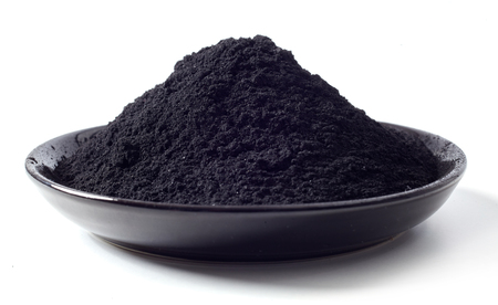Dish heaped with food grade pulverised black charcoal used as an additive in food and drink for detoxification and cleansing of the body Stock fotó