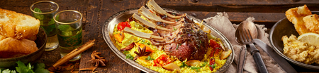 Wide panorama banner of spicy Oriental lamb chops on saffron rice with roasted vegetables served with sides and beverages on an old vintage wooden table Stockfoto