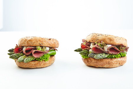 Two healthy fresh green asparagus burgers with sliced ham and mayonnaise on crusty buns viewed to the side on white with copy space Stock Photo