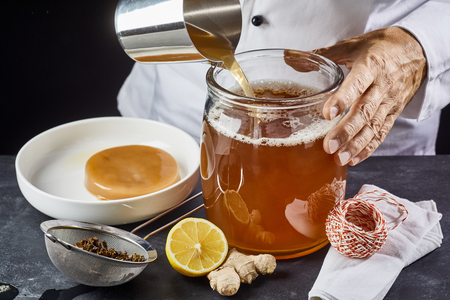 Man pouring a brew of sweetened black tea into a sterilised glass jar ready to add the scoby while making homemade kombucha Stockfoto