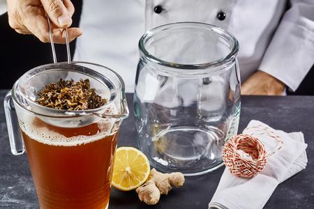 Man preparing kombucha SCOBY tea in jar