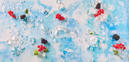 Scattered fresh red currants and blackberries on a cool mottled blue background with crushed ice viewed from above in panorama banner format