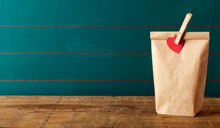 Brown Sack Mittagessen mit Wäscheklammer oben drauf. Beinhaltet Kopierraum über dunkelgrüner Wand und Holztisch.