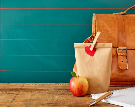 School lunch packed in a recyclable brown paper packet pegged with a red heart and a briefcase with notebook on a desk with copy space behind