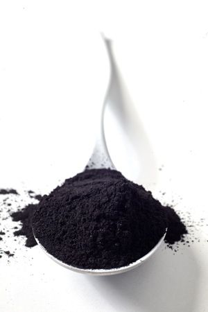 Spoonful of organic activated food grade charcoal used to adsorb toxins and cleanse and detoxify the body