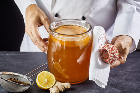 Man preparing to seal a jar of fermenting sweetened black tea with scoby to make kombucha using a white cloth and string